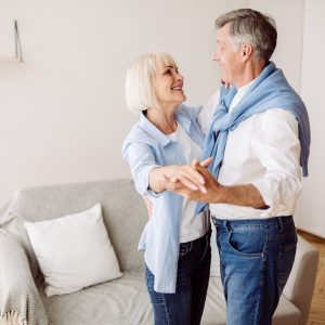 Happy mature couple dancing slow ballroom dance in the living room and looking at each other, free space